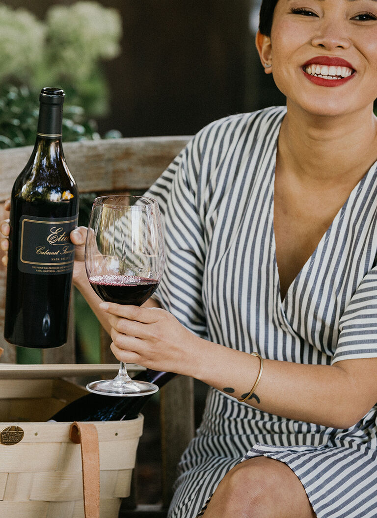 woman holding a glass of Etude cabernet