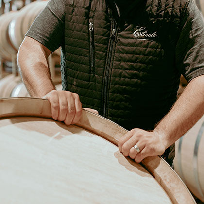 etude winemaker moving a wine barrel