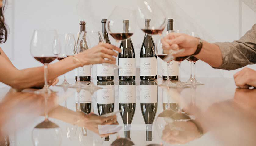 group of people tasting a lineup of pinot noir from Etude